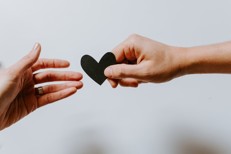 Ein Herz aus Papier von einer Hand in die Andere.